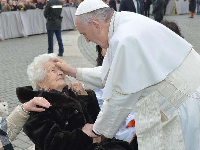 Pope-Francis-makes-the-sign-of-the-Cross-on-the-forehead-of-an-elderly-lady.jpg